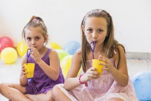 two girls drinking juice